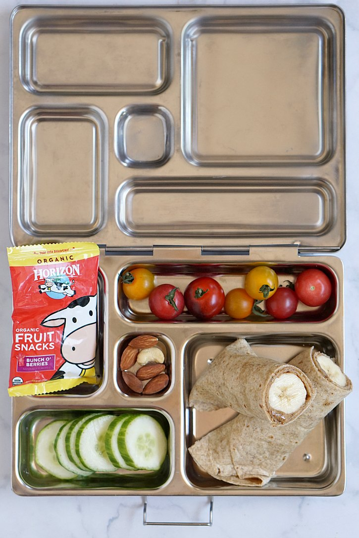 Vegetarian kids lunch box with banana almond butter tortilla wrap, fruit, veggies, nuts, and Horizon fruit snacks.