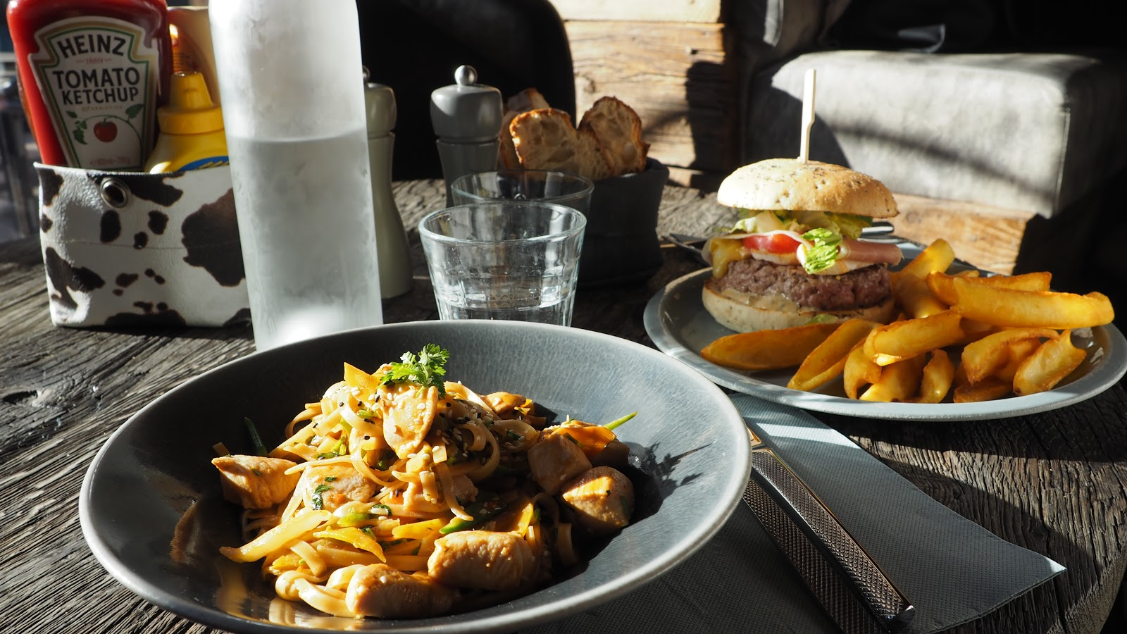 stir fry and burger with chips on a wooden table La Baraque in Val d'isere, France
