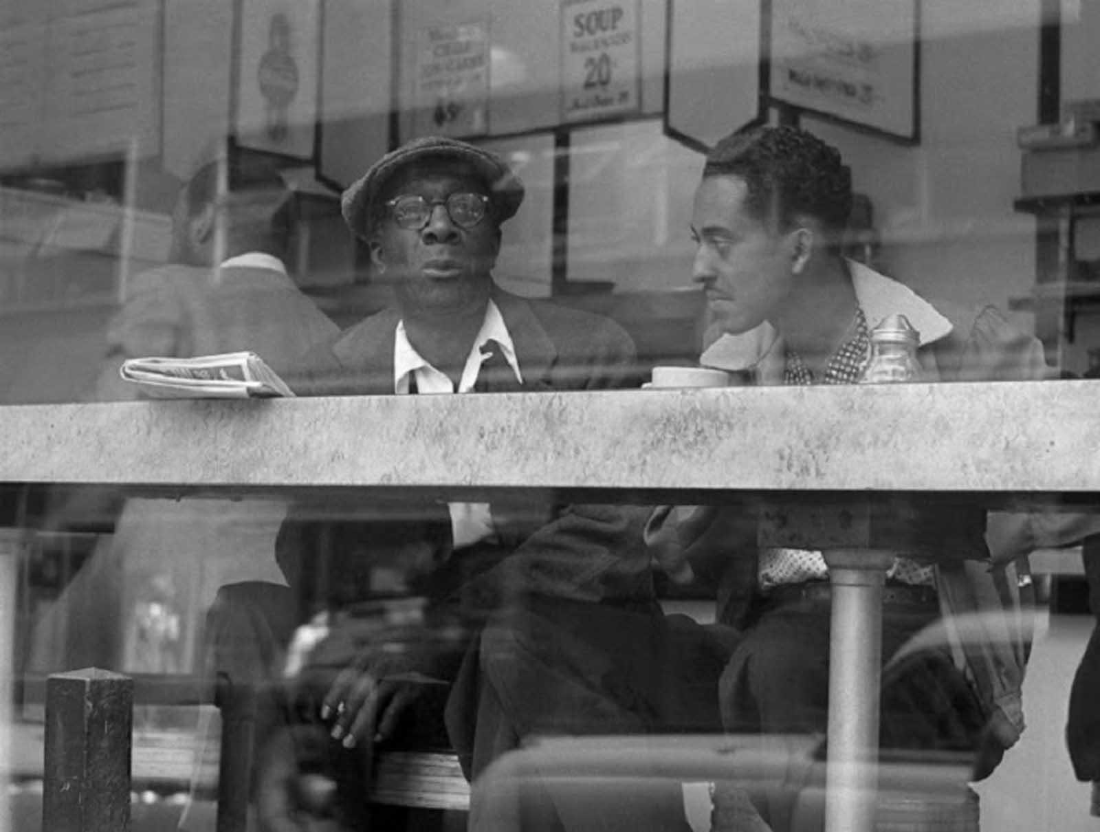 Two men have a conversation in a coffee place near Times Square in April of 1954.