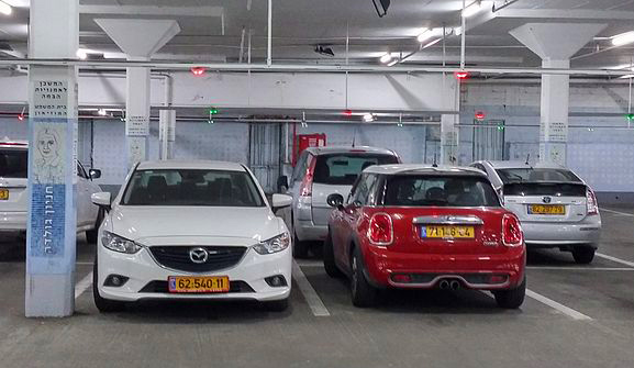 Cars parked in an underground car park with occupancy lights.