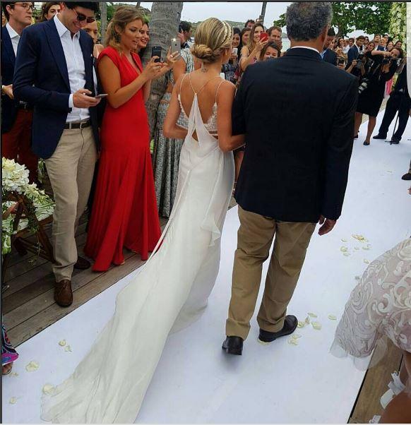 Foto de Helena Bourdon entrando com o pai, parte de trás do vestido de costas