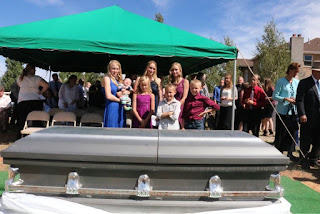 (Photo courtesy Mason Browning) Rachel Jeffs, center, wearing black, stands with her children next to her mother's casket on Aug. 30, 2018, in Centennial Park, Ariz. Her mother, Barbara Jeffs, died of cancer in 2004 at the Fundamentalist Church of Jesus Christ of Latter-Day Saints ranch near Eldorado, Texas. Bodies buried at the ranch have been removed in anticipation of a sale of the property.