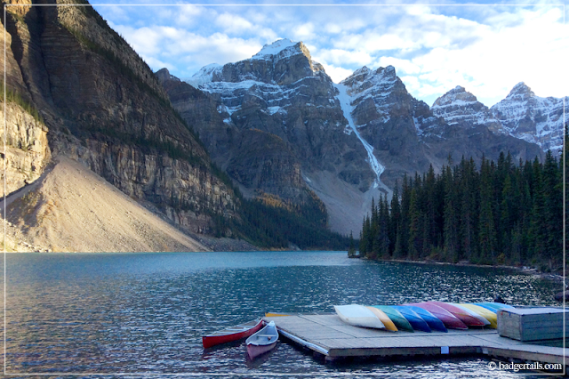 Sunset over Moraine Lake, Alberta, Canada with Colourful Canoes piled on decking. Canadian Rockies. > See more on Badgertails.com <
