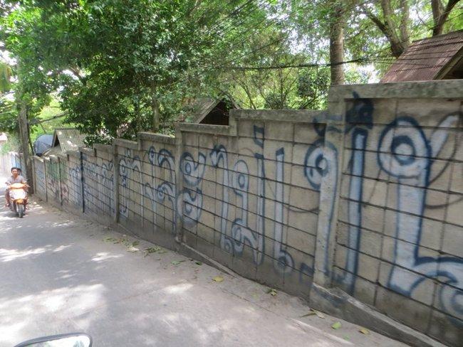Забор расписан на тайском языке