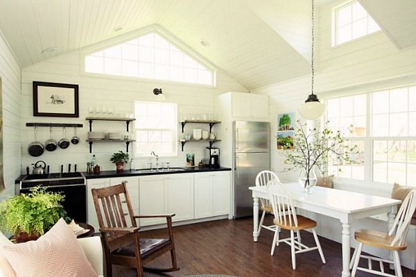 All white cottage interior of a cozy bright small kitchen and dining area