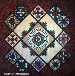 Quilt composed of hand-pieced sampler blocks around a large compass medallion.