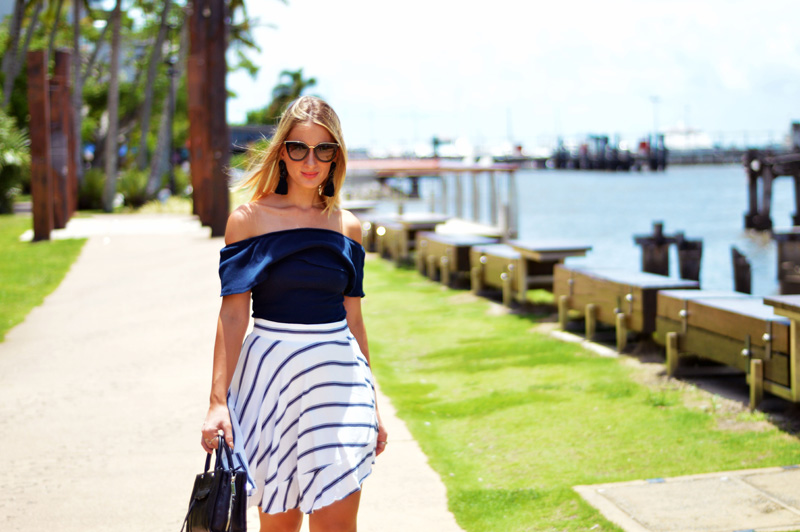 australian style blogger wearing prada sunglasses striped skirt navy off shoulder top and rebecca minkoff bag walking down cairns wharf