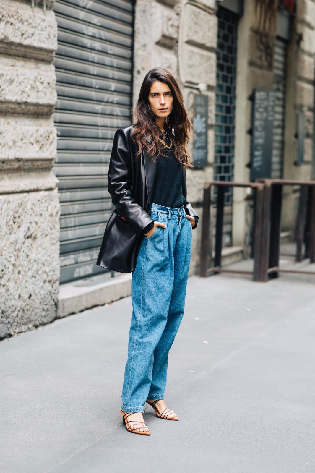 How to Wear 80s-Inspired Pleated Jeans — Street style outfit with black leather blazer, gold chain necklace, denim, and strappy sandals