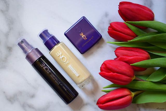 Kosmetyki marki The ONE Oriflame: zestaw korektorów, podkład i mgiełka utrwalająca makijaż