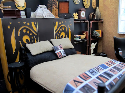 One-twelfth scale miniature scene, with a bed dressed in linen and black with throw rug and cushion printed with letter As, in front of a false wall.