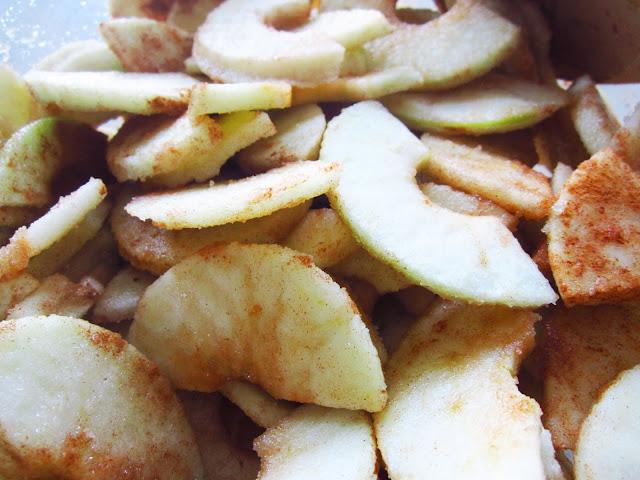 cut and peeled Granny Smith apples coated in cinnamon and sugar for a pie filling