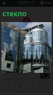 Высотное здание в городе целиком покрыто стеклом, в котором отражаются другая архитектура
