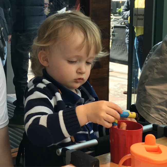 toddler sat at table with crayons