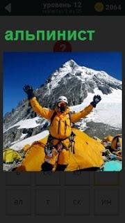 Около палатки на фоне вершины стоит альпинист с раскинутыми руками тепло одетый