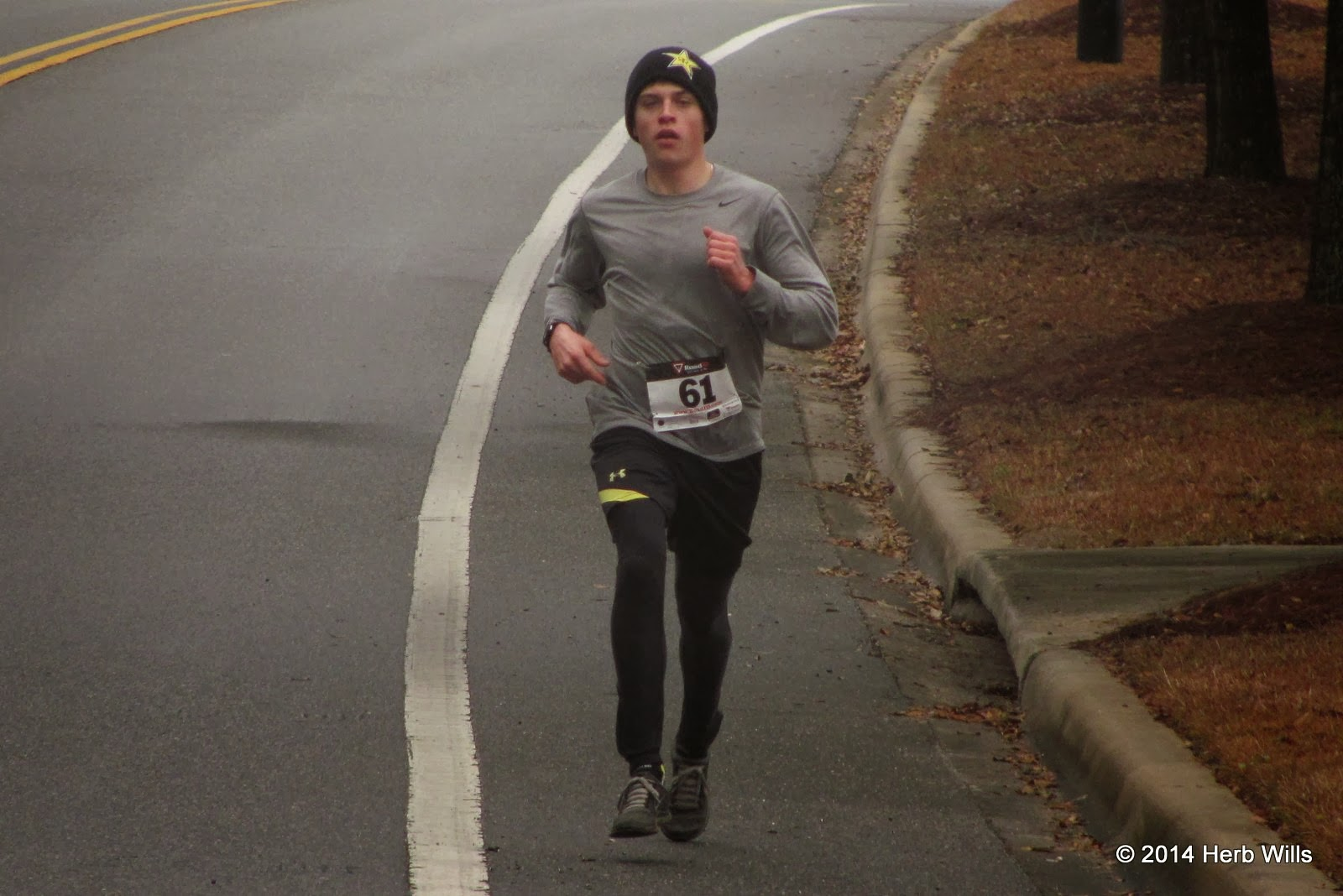 Bundled up for much colder conditions, Justin Martin (1st, 16:55) leads the 2014 2-1-1 Big Bend 5K on Schoolhouse Road, about two kilometers into the race
