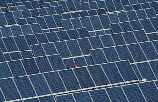 An employee walks between rows of solar panels at a solar power plant on the outskirts of Dunhuang, Gansu province, China, June 10, 2011. (Credit: Reuters/Stringer/File Photo) Click to Enlarge.