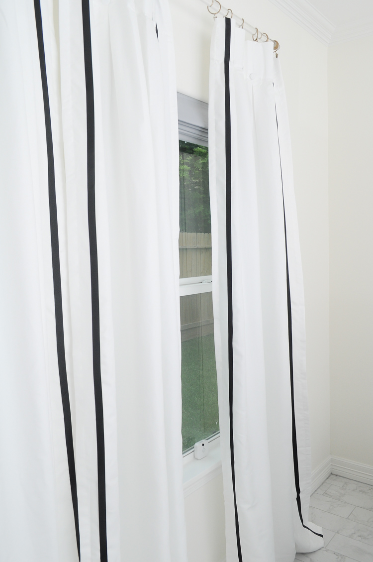 Plain store bought curtains get spruced up with some black grosgrain ribbon on a lucite rod.
