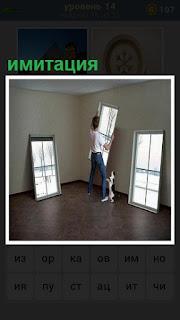парень в комнате расставляет имитацию окон на картинах