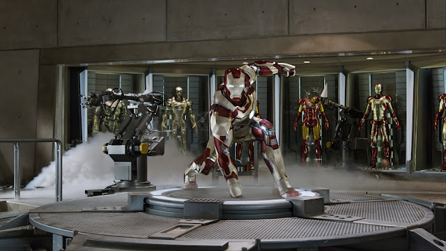 Iron Man, posing in his new armor for the film, in front of all his old armors.