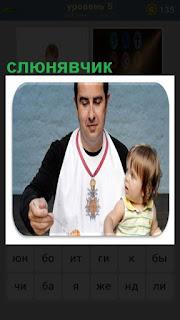 мужчина в слюнявчике кормит на коленях ребенка кашей