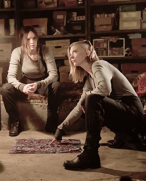 Na imagem: Cena de Jogos Vorazes com a Cressina agachada apontando para um mapa no chão enquanto olha para alguém em pé fora da imagem. Atrás dela está Katniss sentada sobre uma caixa com os braços apoiados na perna e olhando para Cressida