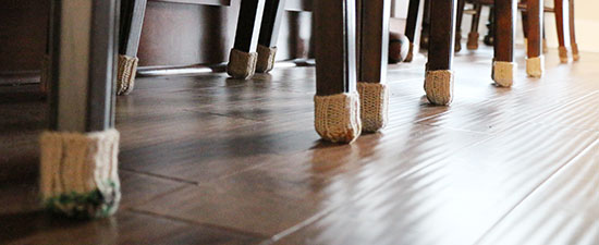 Bottoms of bar stool legs wearing hand-knit furniture socks on a dark wood floor.