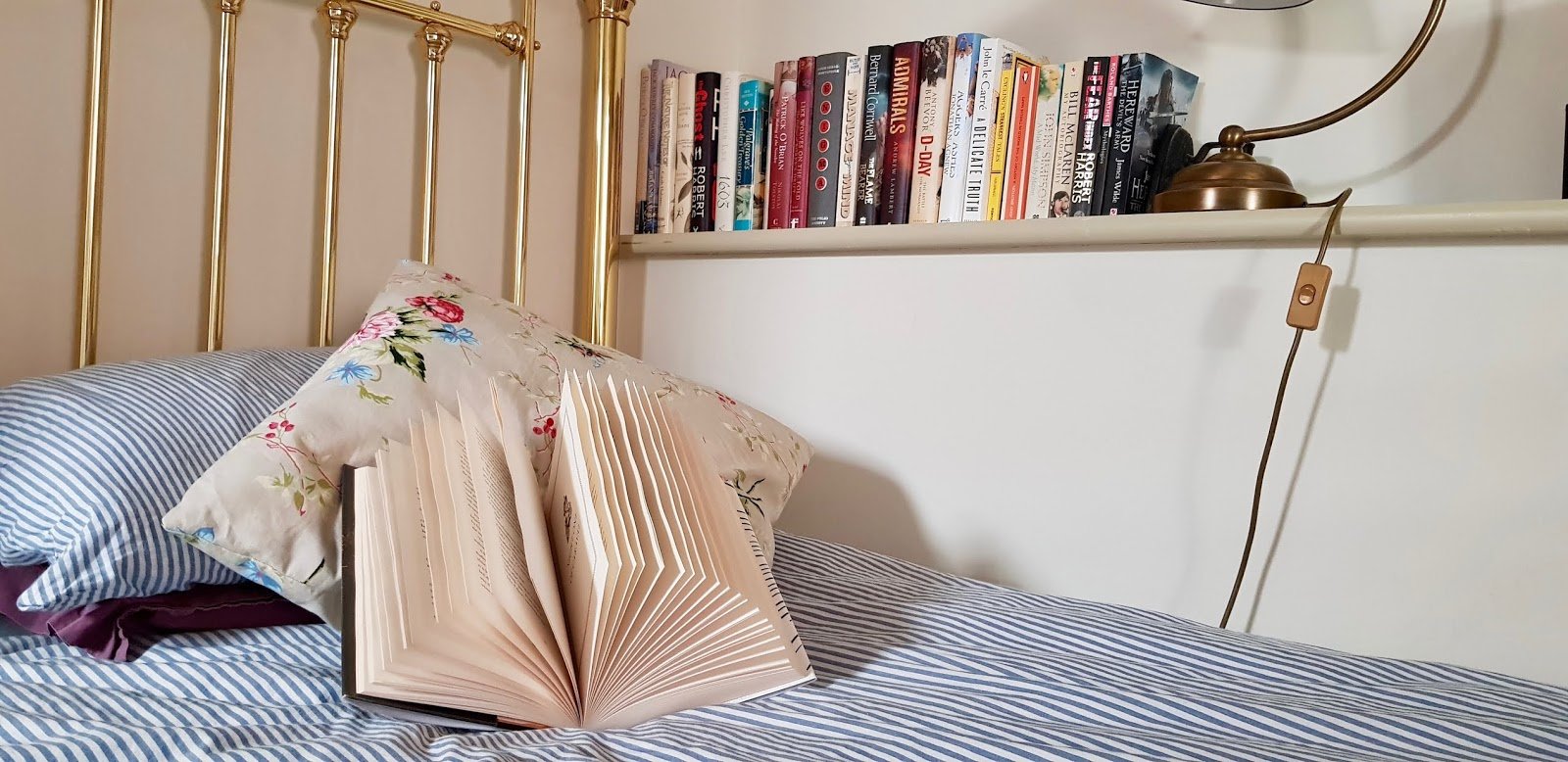 n open book rests on a pillow on a bed with a blue stripe duvet cover, with a shelf of books in the background