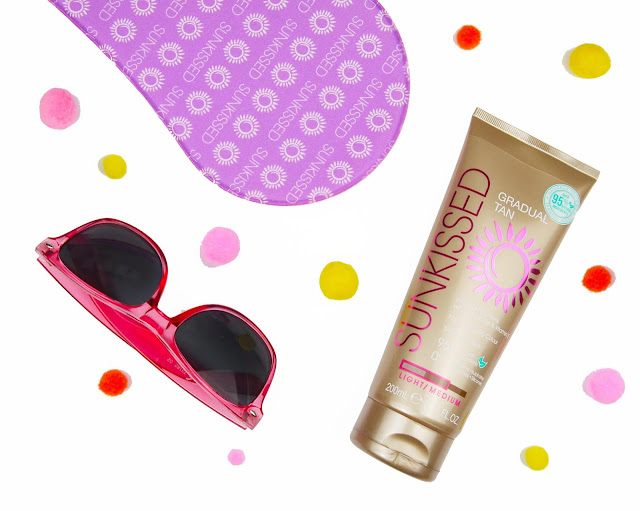 a pair of pink sunglasses, a purple fake tanning mitt, and a bronze tube of gradual tan on a white background
