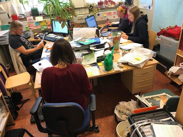 Sama täysi toimisto kuin ensimmäisessä kuvassa, mutta nyt myös neljä ihmistä työn teossa.