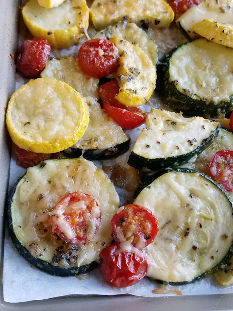 parmesan roasted zucchini and cherry tomatoes on a sheet pan