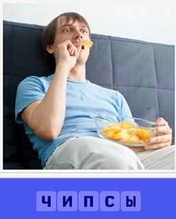 сидя на диване парень ест чипсы из тарелки