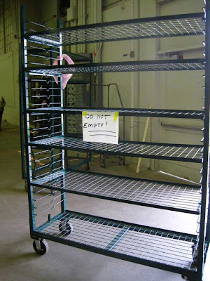 Empty green wire multi-shelves rolling cart with a hand-written sign on it that reads DO NOT EMPTY!