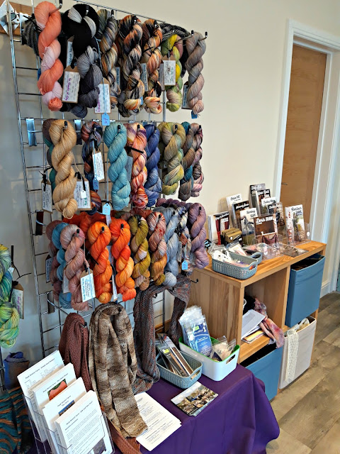 More hand-dyed yarns in various colours ranging from black to shades of orange hanging on wall racks.