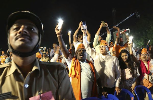 Supporters of the Bharatiya Janata Party hold their cellphones and shout slogans