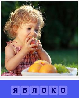 сидит девочка и перед ней тарелка с фруктами, ест яблоко