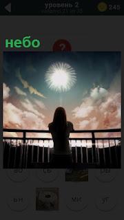 Женщина около парапета смотрит в небо, на котором плывут облака