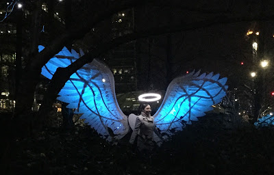Pic of lady standing under the halo of the artwork with angel wings lit in blue