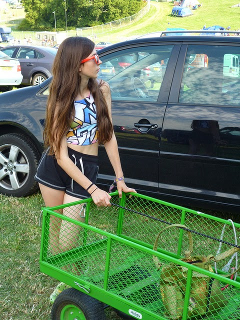 young teen girl in shorts and sunglasses with festival trolley
