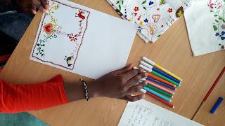 Um aluno a escolher as cores para pintara o seu postal com desenhos inspirados nos lenços dos namorados portugueses