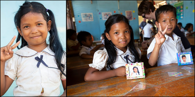 Young Cambodian girl poses for her portrait. Then showing her decorated framed photo.