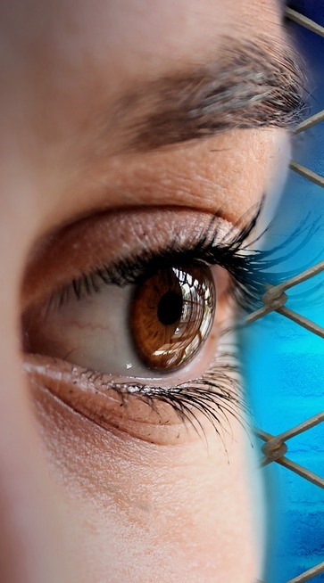 partial woman's face with dark circles standing near a fence.jpeg