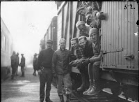 A black and white photograph of a group of smiling people leaning out of a railroad car.