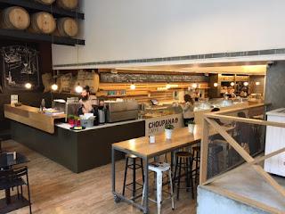 Espaço do Choupana Caffé com mesas, cadeiras e balcão de atendimento