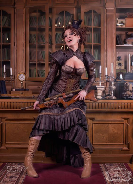 woman wearing purple steampunk costume, matching corset, skirt and tailcoat. She also wears a mini top hat fascinator, brown boots and carries a rifle.