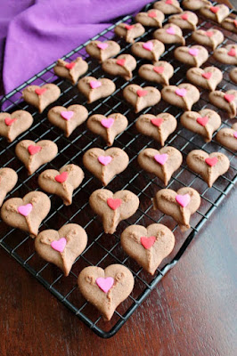 cooling rack full of chocolate spritz heart cookies with heart sprinkles