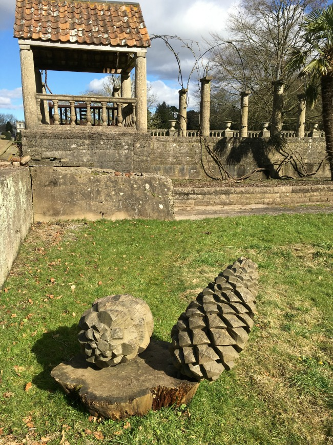 Two Fir cones carved from a tree stump with classic columns above