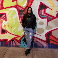 Lilliam Rivera in jeans and black leather jacket, standing before a graffiti mural wall