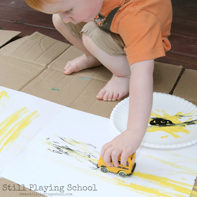Toddler process art painting with school bus