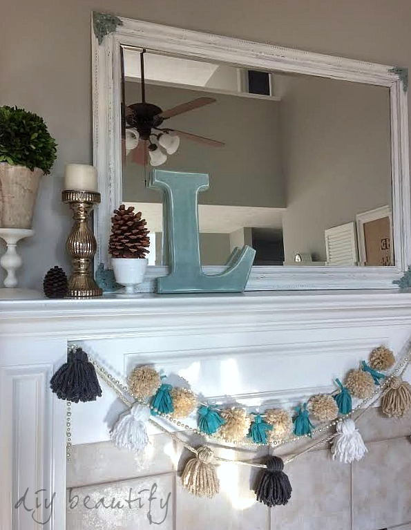neutral mantel with pops of color in the monogram and tassel garland