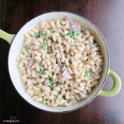 green saucier full of pasta with ham peas cream and parmesan cheese